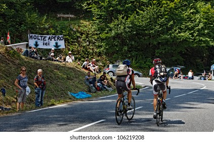 EAUX-BONNES,FRANCE-JUL 15:Two amateur cyclists climbing the road to Col D'Aubisuqe,in Pyrenees Mountains, before passing the peloton during the 13 stage of Le Tour de France on July 15 2011.