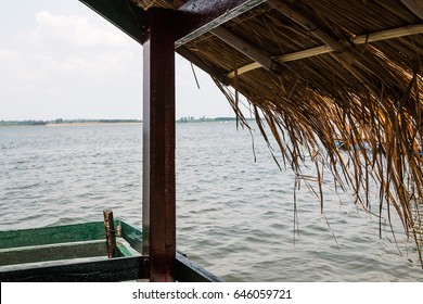 eaves of straw hut with water and sky background
