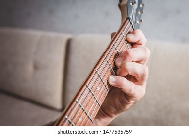 Eb chord - close-up male Caucasian hand takes a chord on a 6 string guitar