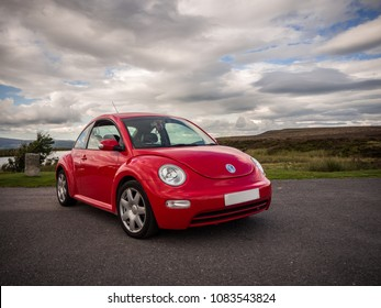 Ebbw Vale, Wales, UK: August 4, 2017: New Shape Red compact car Volkswagen Beetle, parked in the Welsh Countryside