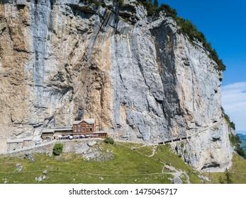 Ebenalp, Switzerland - August 09, 2019 : Aerial view of the guest house Aescher - Wildkirchli against the Ascher cliff at the mountain Ebenalp over the Swiss Alps in Appenzell region, Switzerland