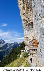 Ebenalp, Switzerland - August 09, 2019 : Guest house Aescher - Wildkirchli against the Ascher cliff at the mountain Ebenalp over the Swiss Alps in Appenzell region, Switzerland