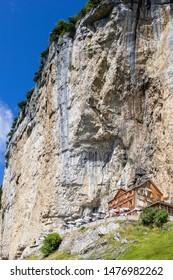 Ebenalp, Switzerland - August 09, 2019 : The guest house Aescher - Wildkirchli against the Ascher cliff at the mountain Ebenalp over the Swiss Alps in Appenzell region, Switzerland