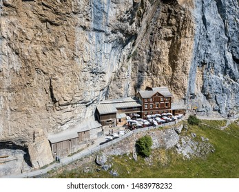 Ebenalp, Switzerland - August 09, 2019 : Aerial view of the guest house Aescher - Wildkirchli against the Ascher cliff at the mountain Ebenalp over the Swiss Alps in Appenzell region, Switzerland