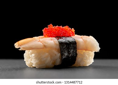 Ebi nigiri sushi on black stone plate. Rice with shrimp, wrapped in nori strip and topped with red flying fish roe.