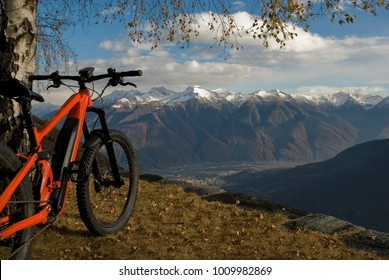 ebike, e-bike, electric bicycle, high mountain, leaning against tree, detail of handlebars, wheels, saddle, display, alps landscape, snow covered tops, winter, Antrona Valley, Piedmont, Italy