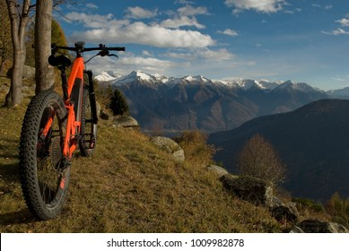 ebike, e-bike, electric bicycle, high mountain, leaning against tree, detail of handlebars, wheels, saddle, display, alps landscape, snow covered tops, autumn, winter, Antrona Valley, Piedmont, Italy
