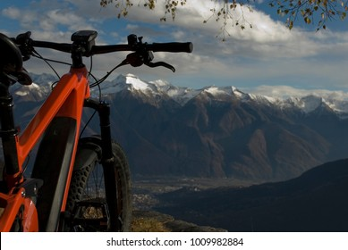 ebike, e-bike, electric bicycle, high mountain, leaning against tree, detail of handlebars, wheel, saddle, display, alps landscape, snow covered tops, winter, Antrona Valley, Piedmont, Italy