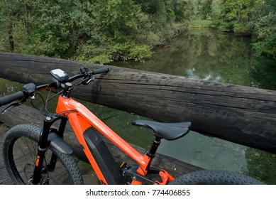 Ebike E-bike electric bicycle orange, detail of handlebar and wheel, leaning on an old dark wooden bridge, in the woods, beneath which flows a light green mountain river, plant, Ossola, Alps, Italy