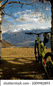 ebike, e-bike, electric mtb, pedelec, high mountain, leaning against tree, detail of handlebars, wheels, saddle, display, alps landscape, snow covered tops, autumn, Antrona Valley, Piedmont, Italy