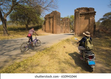 E-bike is the environmentally friendly way of sightseeing in Bagan. One traveler on e-bike with a local boy passing  by on bicycle at Tharabar Gate, Old Bagan, Myanmar.