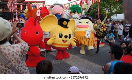 EBINA, KANAGAWA PREFECTURE, JAPAN - JULY 26, 2014: Local people watch the yurukyara mascots playing music and dancing Bon Odori with performers in a summer matsuri festival at Ebina Central Park.