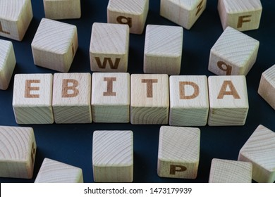 EBITDA, Investment term Earnings before interest, taxes, depreciation, and amortization concept, cube wooden block with alphabet combine the word EBITDA on black chalkboard background.
