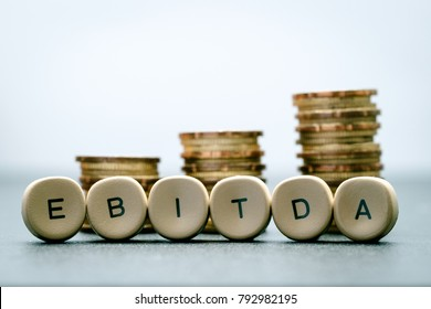 EBITDA letter blocks  and stacked coins. EBITDA stands for Earnings Before Interest, Taxes, Depreciation and Amortization.