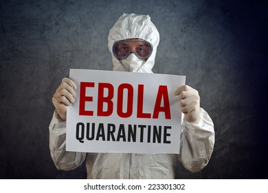 Ebola Quarantine sign held by medical health care worker wearing protective gown, gloves, mask and goggles.