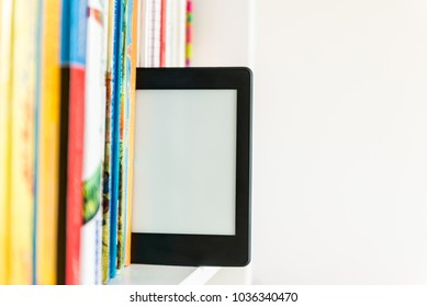 Ebook or digital reading tablet device standing on the shelf with bright real books