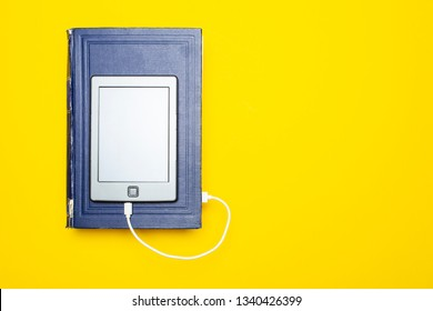 E-book lies on the old thick book, connects to it with a cable by downloading information from there, with a copy space. Concept of modernization technology and simplification of educational process.