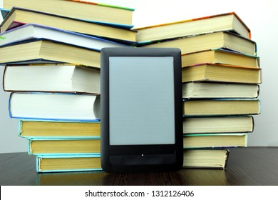 E-book on the background of a stack of old books.Changing media of information from paper to eletronic.