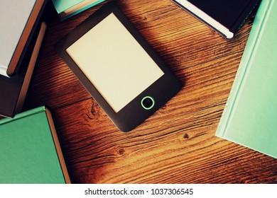 E-book reader and books on wooden background . Top view