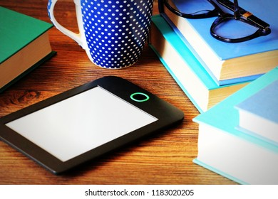 E-book reader and books on wooden background .Education background
