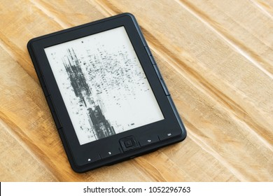 E-book reader with broken screen laying on the wooden table