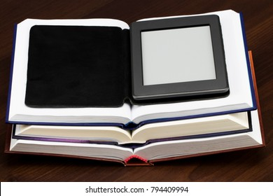 E-book reader device on desk in library. Alternative for traditional books.