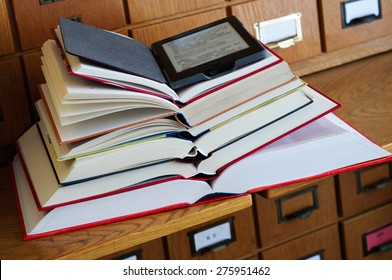 E-book Reader on top of Stack of Books in a Library