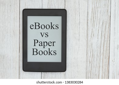 Ebooks vs paper books message on an e-reader screen on a weathered whitewash desk