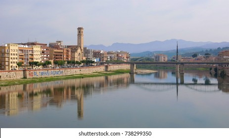 Ebro River reflects the buildings of Tortosa, Catalonia, Spain in early morning light