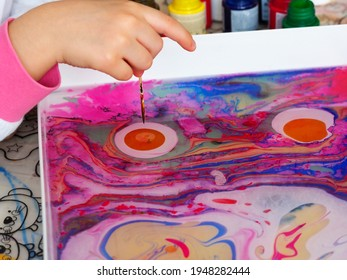 Ebru painting. Traditional Turkish marbling art. Little girl is doing water painting activity at home. Stay home activity for students.