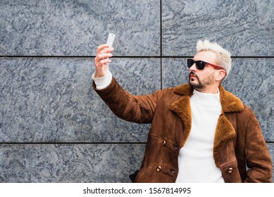 eccentric bearded man with platinum blonde hair and sunglasses takes pictures of himself with his smartphone, funny hipster posing for selfie