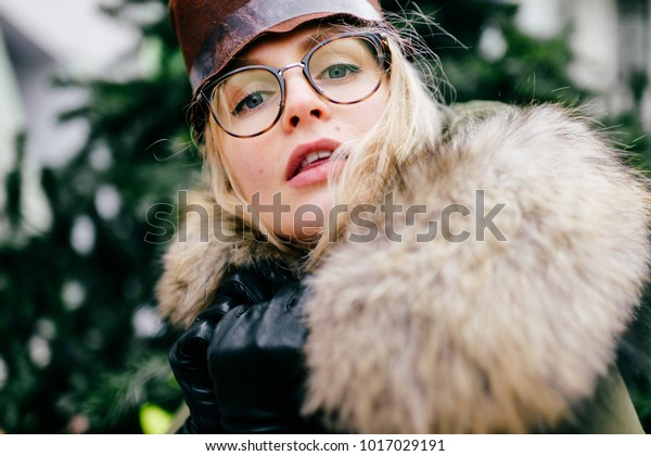 Eccentric female in glasses and hat portrait. Funny young beautiful girl fooling . Beautiful artistic model in jacket with faux fur making funny faces. Old fashioned style aristocrat bizarre woman