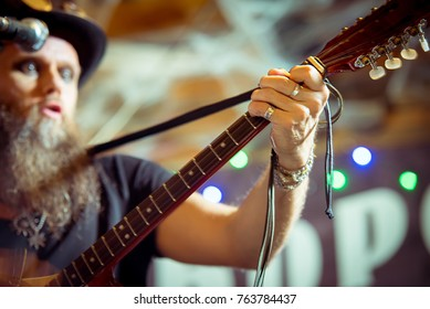 eccentric man in a hat performs at a music bar. Sings songs and plays Irish bouzouki (girar) blurred motion