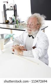 Eccentric smiling senior scientist in his lab with blackboard and pointer.