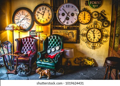 An eccentric vintage living room armchairs with many clocks on the wall background in an antique shop on the Iseo Lake - Brescia - Italy, 16 Feb 2013