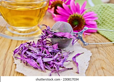 Echinacea dried in a metal strainer and paper, fresh flowers on a wooden boards background