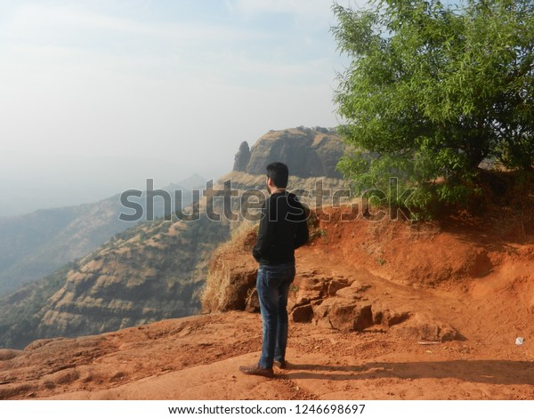 echo point , Matheran , maharashtra,India, 28th november 2018: a guy standing on a valley echo point sun set point.