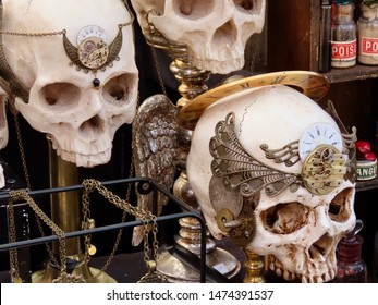 Echternach / Luxembourg - 08/03/2019: Merchandise in a goth steampunk themed street market: macabre plastic skulls with bronze ornaments attached, bottles with partially visible labels