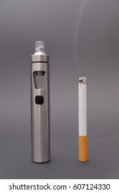 e-cigarette with normal cigarette on grey background