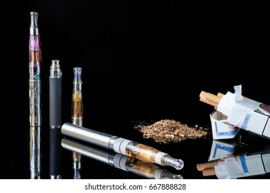 E-cigarette with pile of grinded tobacco leaves and a pack of smokes