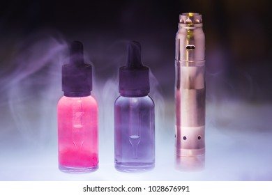 E-cigarette with two e-liquid in the white smoke on a dark background. E-juice from vape. Alternative to smoking