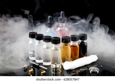 E-cigarette vapor with juice bottles, screwdriver and cotton wick with tools