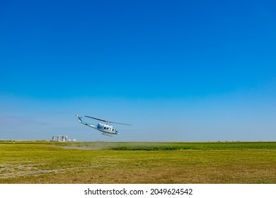 Ecka, Vojvodina, Serbia - August 21, 2021: National Parachuting Championship Helicopter takes off from the green meadow and flies low horizontally.