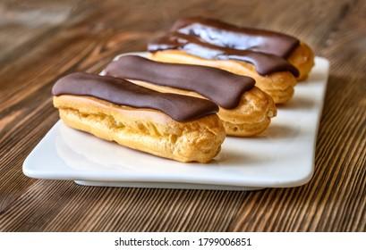 Eclairs mit Schokoladenpfeifen auf Servierplatte