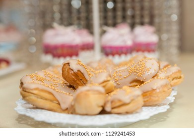 Eclairs and cupcakes/Selective focus of a platter of eclairs with pink cupcakes in the backdrop.
