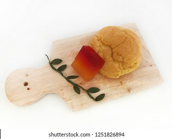 eclairs and jelly with wooden cutting board.