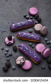 Eclairs, macarons, blackberries and blueberries on dark concrete background. Overhead view