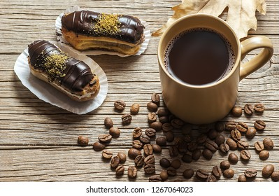 Eclairs with pistachio and black chocolate  with custard on wooden background near cup of coffee with coffee grains . Traditional French dessert. Eclair Pastery concept