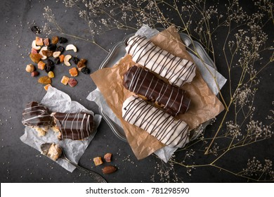 Eclairs or profiteroles with black chocolate and white chocolate with custard inside on a metal plate on a dark background. Traditional French dessert. Empty space for design text template