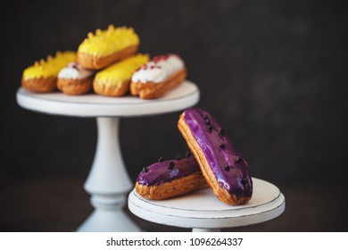 Eclairs with taste of lemon, black currant, vanilla on cake stand over grey table
